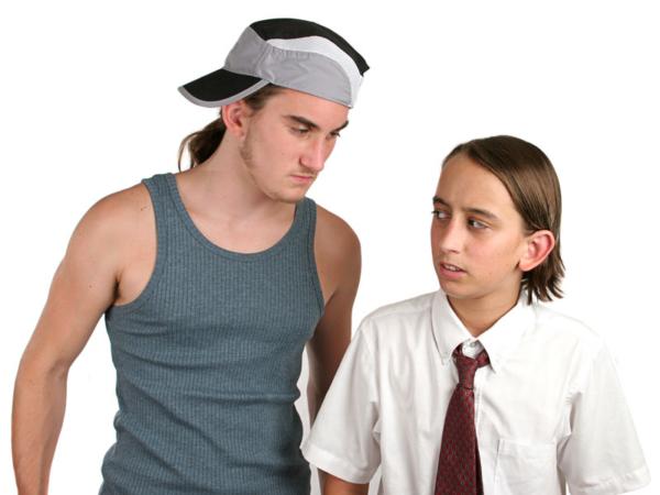 Teenage boy bullying another boy.