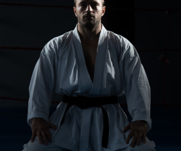 Man in martial arts uniform meditating.